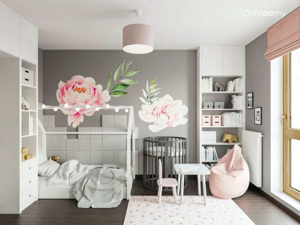 Łóżko domek i drugie rosnące z dzieckiem łóżko dla niemowlaka w pokoju dwóch dziewczynek z szarymi ścianami i naklejkami piwoniami