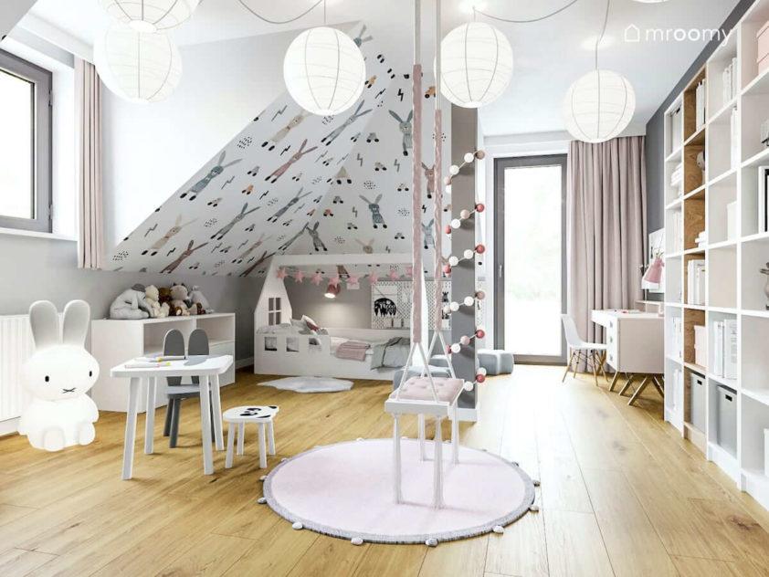 Pokój ze skosami dla małej dziewczynki z huśtawką łóżkiem typu domek w kolorach białym i pudrowego różu