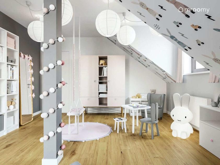 Kącik do czytania dla dziewczynki obok szafy stoliczka i lampy królik w pokoju na poddaszu
