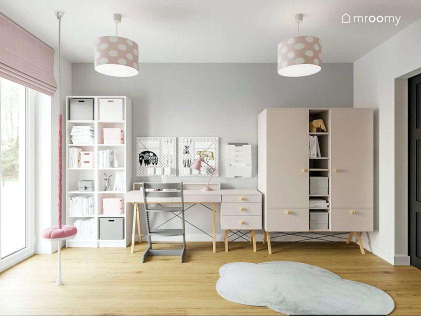 Białe drewniane i delikatnie różowe meble w pokoju wczesnoszkolnej dziewczynki z szarą ścianą i abażurami w grochy
