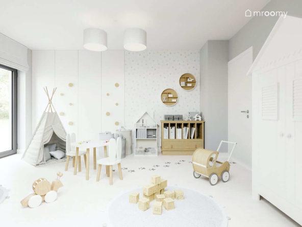 Jasny pokój małej dziewczynki z meblami z jasnego drewna okrągłymi uchwytami na białej szafie i szarym tipi