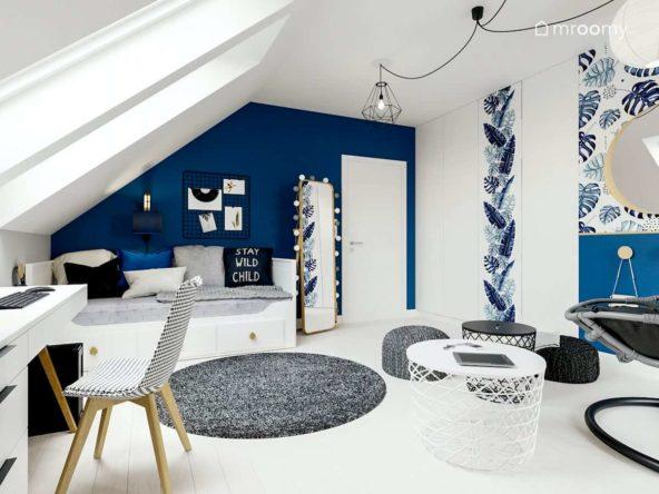 Biało-granatowy pokój nastolatki z białym łóżkiem okrągłymi dywanami i metalowym stolikiem