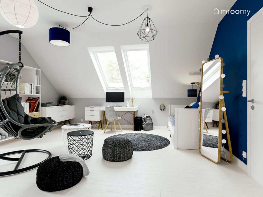 Białe meble z drewnianymi nożkami stojące lustro i niebieskie dodatki w poddaszowym pokoju nastoletniej dziewczynki