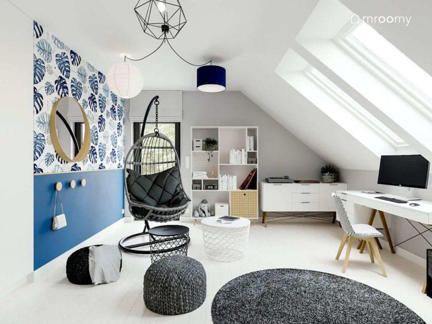 Niebieska tapeta w kwiaty bujany fotel i białe meble w pokoju nastolatki na poddaszu