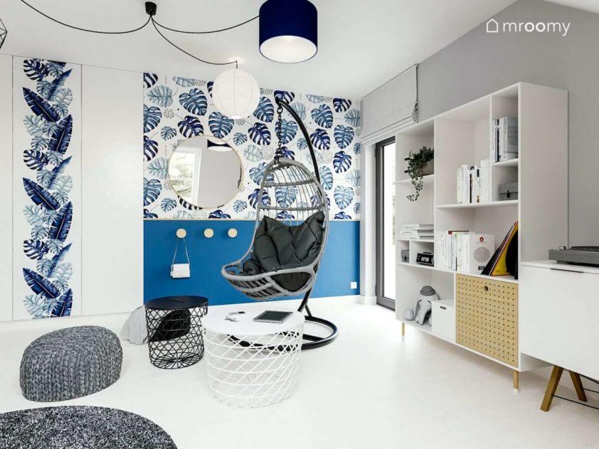 fotel na tle niebieskiej ściany z motywem roślinnym biała podłoga i wiele abażurów w lampie w pokoju nastolatki