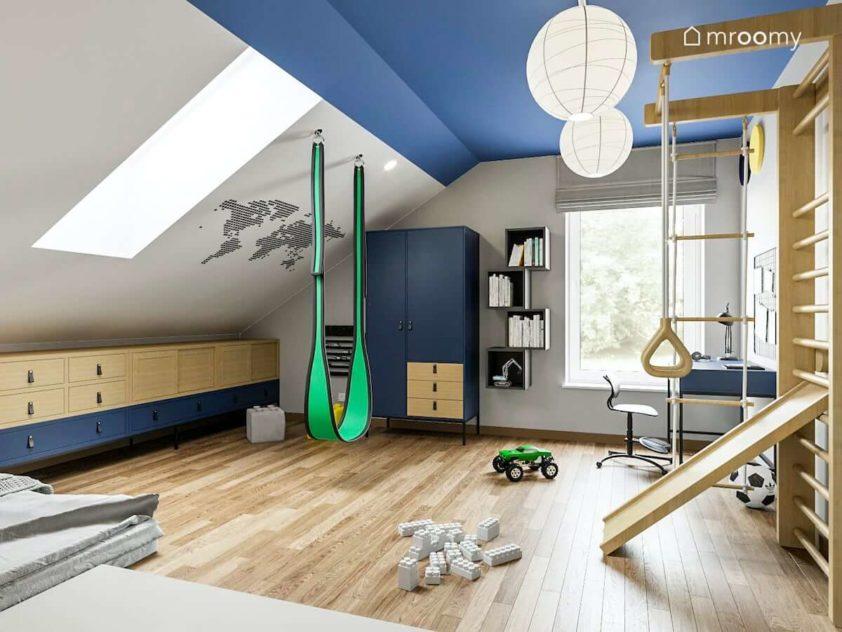 Meble w kolorze niebieskim i naturalnym w pokoju sześciolatka z mapą na poddaszowym skosie kolorowym sufitem i drabinka gimnastyczną