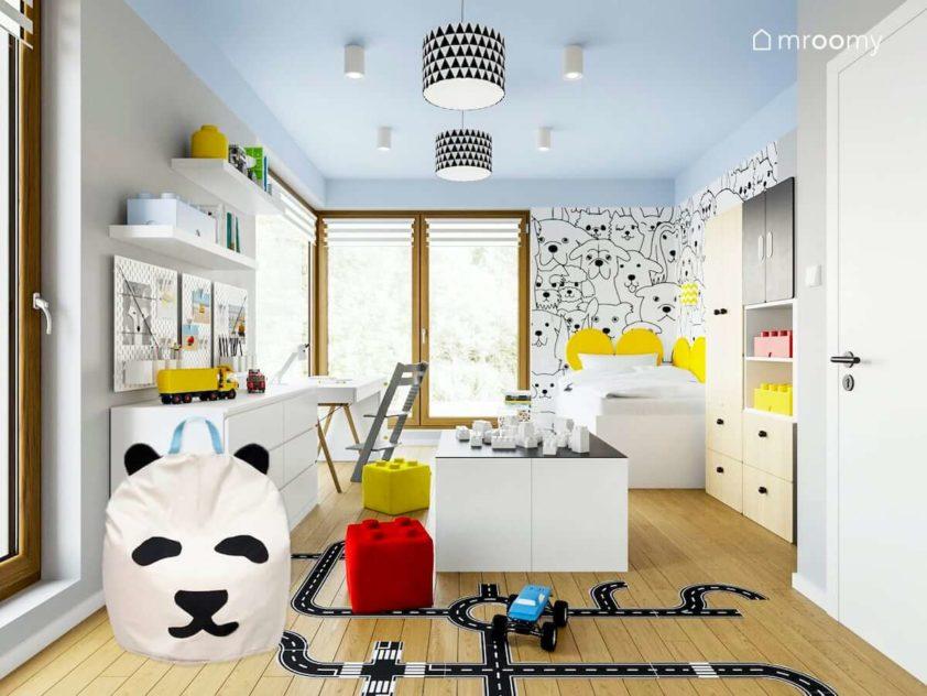 Białe meble naklejki podłogowe drogi miękkie pufy lego tapeta w misie niebieski sufit i białe łóżko w rogu pokoju chłopca idącego do szkoły