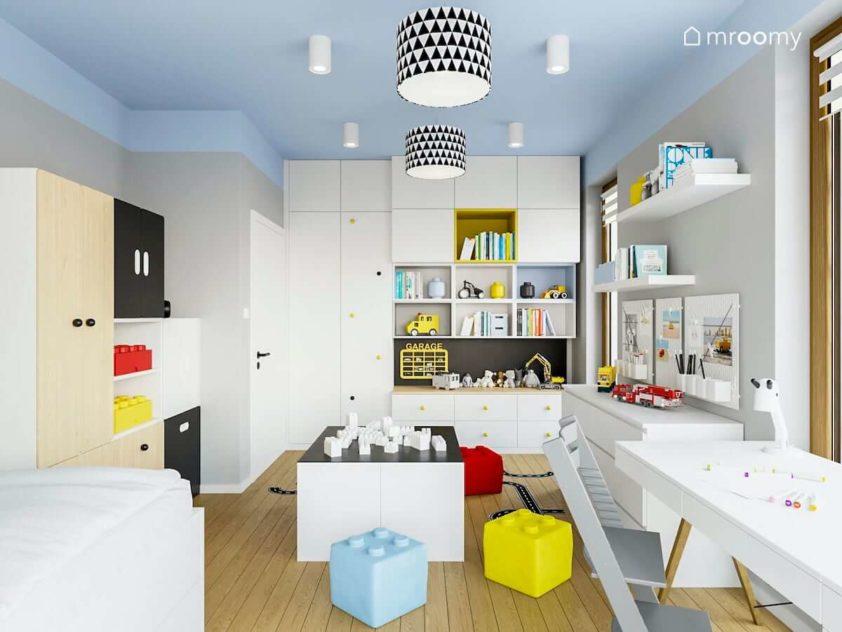 Pokój chłopca w jasnej tonacji z kolorowym sufitem białą szafą niskimi regałami do zabawy na środku pokoju i szarymi ścianami
