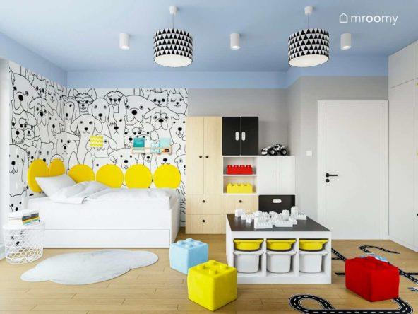Łóżko w kącie z tapetą w pieski żółte okrągłe panele ścienne niebieski sufit i modułowe meble w pokoju chłopca