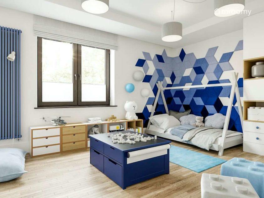 Łóżko tipi niebieskie panele ścienne niebieski stolik do zabawy klockami i regały pod oknem ze sklejki w pokoju małego chłopca