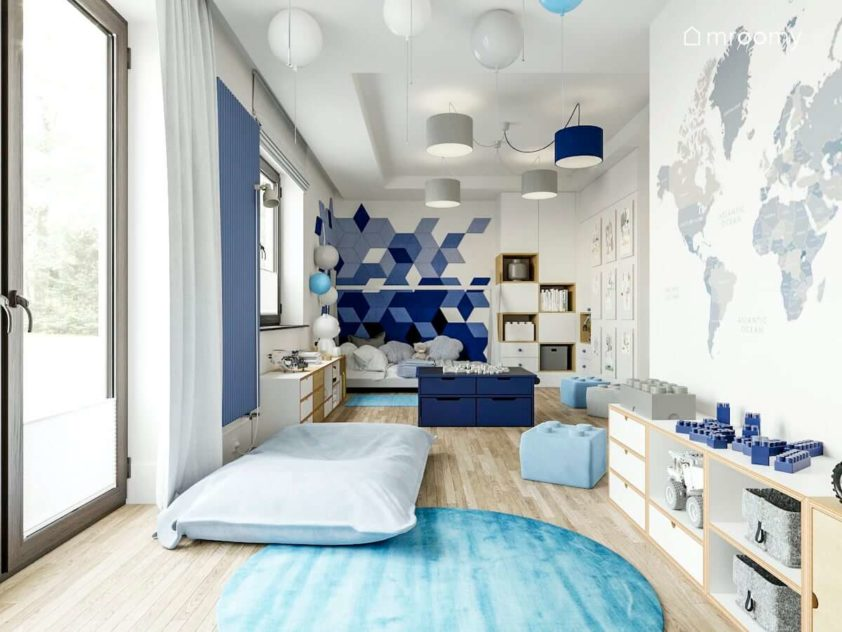 Pokój chłopca przedszkolaka ucznia z łóżkiem tipi niebieskimi miękkimi panelami ściennymi szarymi abażurami lampami balonami tapetą z mapą świata i pufami lego