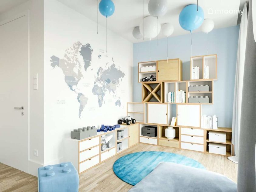 Tapeta z mapą świata modułowe meble ze sklejki naturalnej i białej lampy balony niebieski i szary dywan w pokoju przedszkolaka ucznia