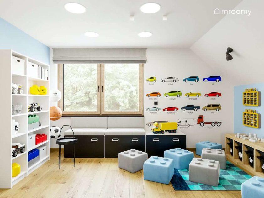 Tapicerowane siedzisko pod oknem tapeta w kolorowe samochodziki pufy w kształcie klocków lego w poddaszowym pokoju małego chłopca przedszkolaka