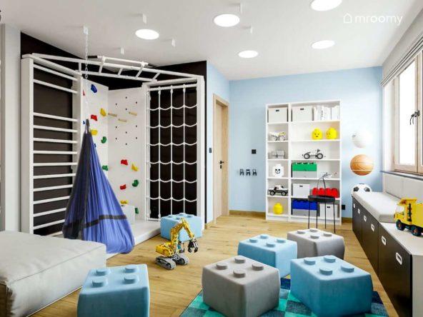 Kącik sportowy z białą  drabinką gimnastyczną i ścianką wspinaczkową pufy lego i niebieskie ściany w pokoju małego chłopca