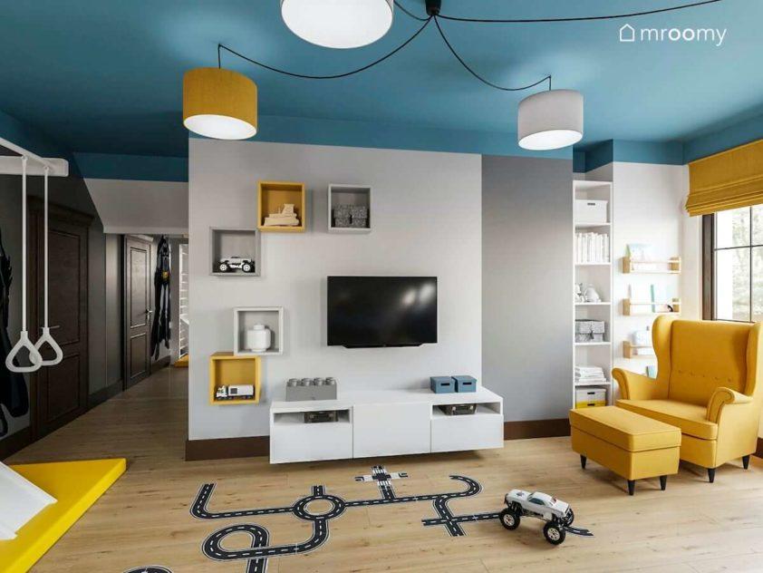 Pokój chłopca ucznia w którym są naklejki podłogowe strefa gier i telewizji niebieski sufit i kolorowe abażury