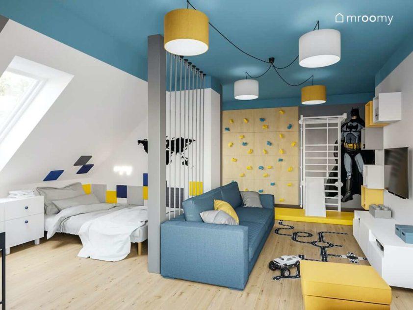 Strefa spania w pokoju chłopca oddzielona od strefy zabawy z sofą ścianką wspinaczkową drabinką gimnastyczną i niebieskim sufitem