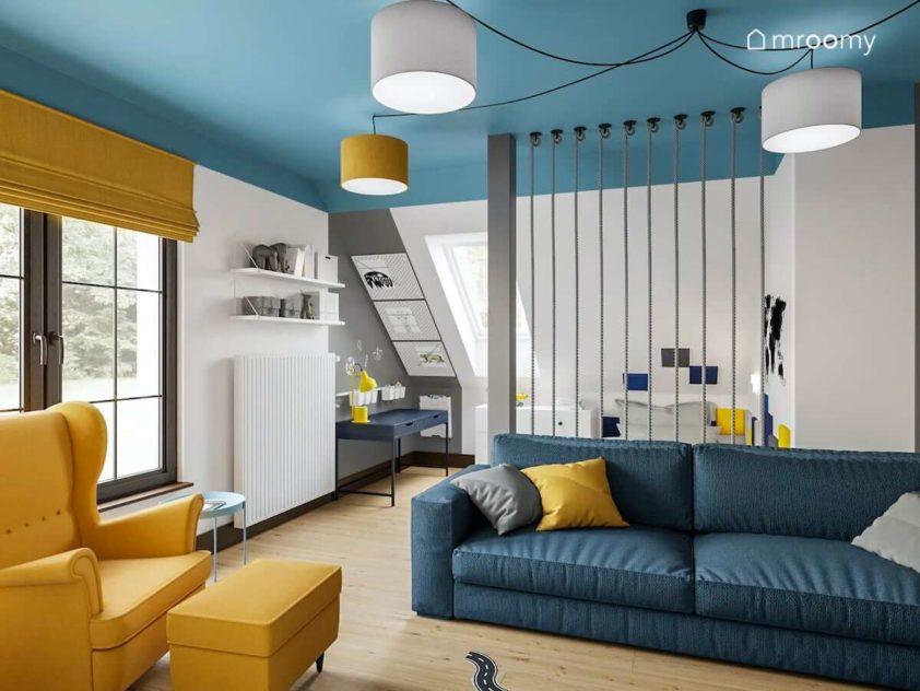 Niebieska sofa żółty fotel uszak niebieskie biurko i białe meble w pokoju na poddaszu chłopca ucznia