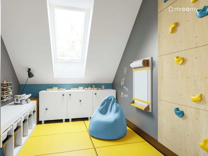 Strefa zabawy w pokoju chłopca z żółtymi materacami niebieskim workiem sako ścianką wspinaczkową i białymi niskimi komodami