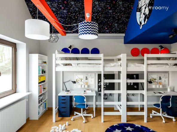Antresole z biurkami pod spodem sufit z tapetą w gwiazdy czerwone belki abażury i kolorowe panele ścienne w pokoju chłopców