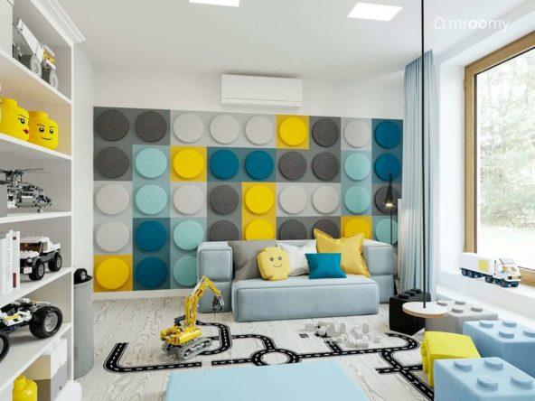Ściana z miękkich paneli w kształcie klocków lego niebieska sofa naklejki podłogowe i huśtawka w pokoju bawialni dwóch chłopców