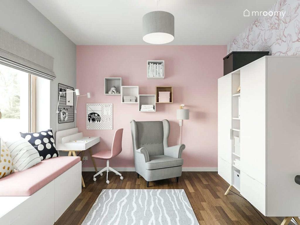 Pokój nastoletniej dziewczynki z szarym fotelem białym biurkiem różową ścianą białą szafą i siedziskiem pod oknem
