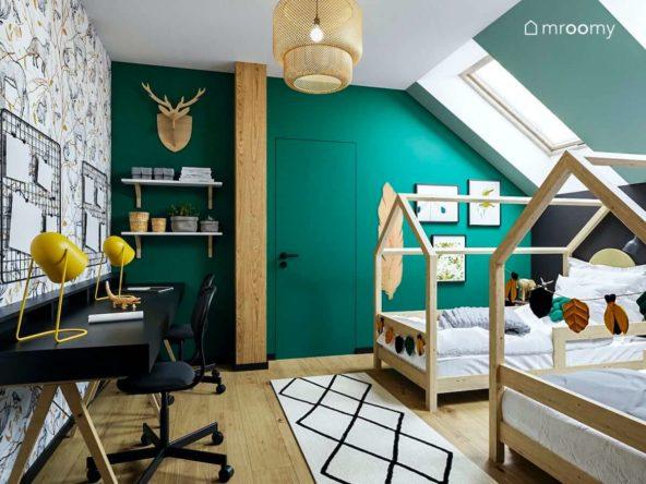 Pokój dla bliźniaków na poddaszu z łóżkami domkami czarnymi biurkami zielonymi ścianami i tapetą we wzory