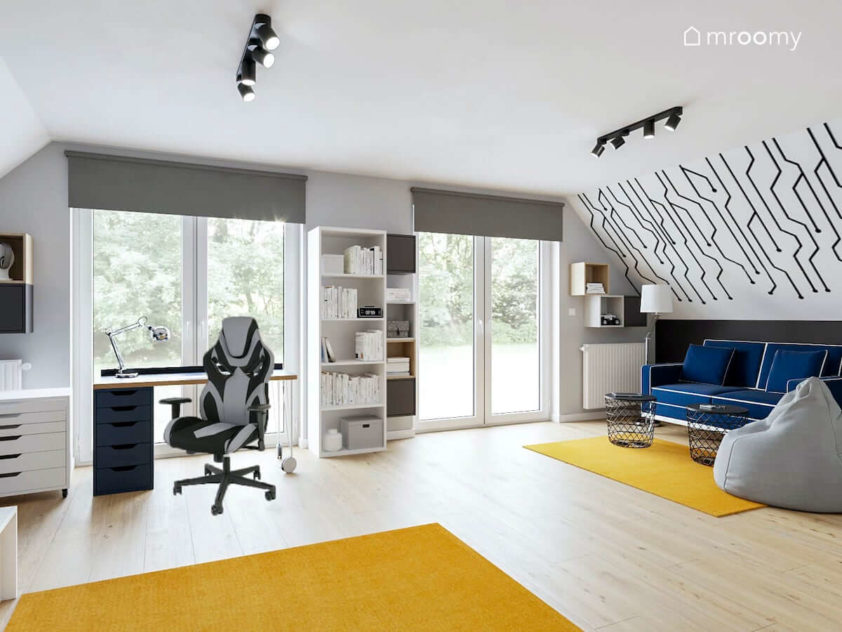 Pokoj chlopca z fotelem gamingowym i granatowa sofa z bialymi lamowkami Na skosie czarno biala graficzna tapeta Na podlodze zolte dywany