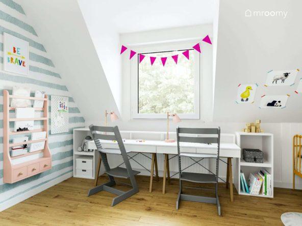Dwa biurka z krzesłami pod oknem na poddaszu obok tapeta w paski i girlanda na oknie w pokoju dla małych dziewczynek