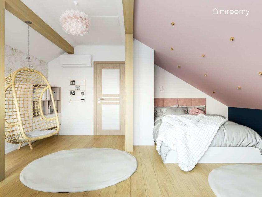 Duże łóżko do spania pod skosem w pokoju nastolatki z różowym sufitem szarym dywanem i belkami z drewna
