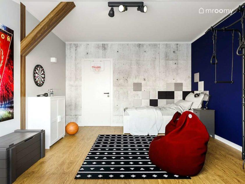 Pokoj nastolatka z tapeta imitujaca betonowe plyty bialymi meblami i granatowa sciana Bordowy worek sako i czarno bialy dywan w pokoju chlopca