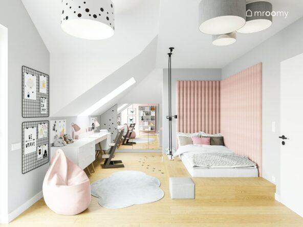 Strefa odpoczynku i strefa nauki w pokoju dziewczynki łóżko na podeście udekorowane miękkimi panelami ściennymi a pod oknem biurko z dużą ilością przestrzeni roboczej na podłodze szary dywan oraz jasnoróżowa pufa