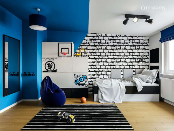 Łóżko szafa z zabawnymi metalowymi nakładkami oraz pufa sako w praktycznym pokoju dla nastolatka ze ścianami pomalowanymi w geometryczne wzory oraz tapetą w cegły