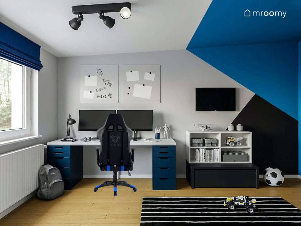 Duże praktyczne biurko tablica magnetyczna i szafka z podestem w pomalowanym w geometryczny wzór pokoju nastolatka