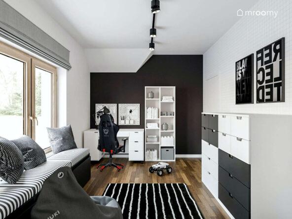 Pokój dla nastolatka utrzymany w tonacji czarno białej z tapetą w zeszytową kratkę a w nim komoda regał oraz biurko z szufladami a także tapicerowane siedzisko dywan w paski i pufa sako