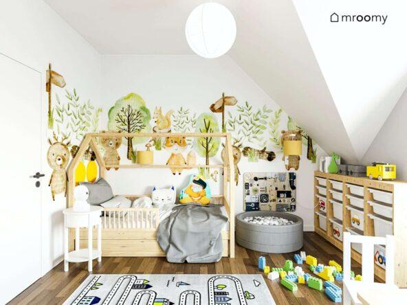 Radosny pokoik dla małego chłopca z drewnianym łóżeczkiem basenem z kulkami i regałem z wieloma praktycznymi pojemnikami oraz tapetą w zwierzątka na ścianie