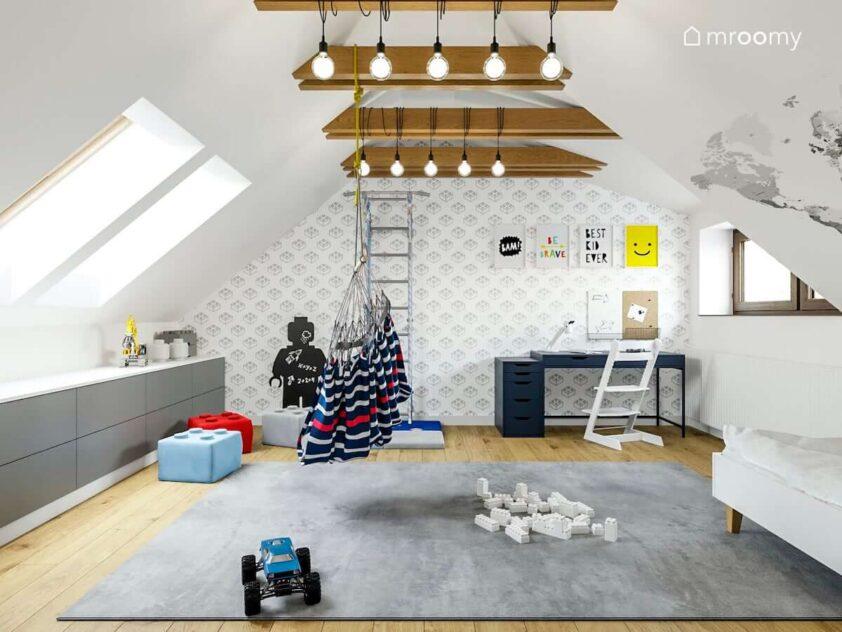Pokój na poddaszu dla chłopca a w nim duży szary dywan biurko drabinka gimnastyczna i pojemne komody na ścianie tapeta w klocki Lego oraz ozdobne plakaty a na suficie lampy zawieszone na belkach sufitowych