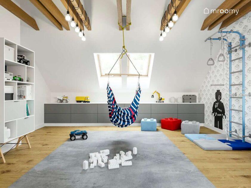 Jasny poddaszowy pokój małego chłopca a w nim białe i szare meble duży dywan drabinka gimnastyczna i podwieszana u sufitu huśtawka