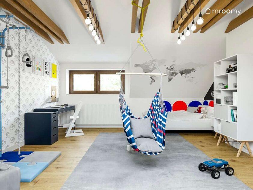 Jasny pokój z białymi ścianami łóżkiem ozdobionym kolorowymi panelami ściennymi niebieskim biurkiem i dużym dywanem w pokoju kilkuletniego chłopca