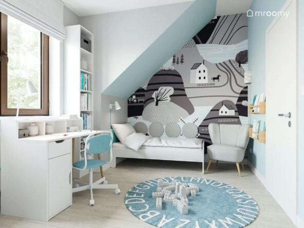 Szara tapeta z rysunkową panoramą oraz białe łóżko wysoki regał biurko i fotel w jasnym pokoju ze skosami dla kilkuletniego chłopca