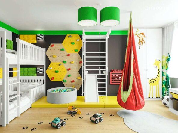 Piętrowe łóżko oraz ścianka wspinaczkowa drabinki gimnastyczne basen z kulkami oraz czerwona huśtawka kokon w pokoju dwóch braci