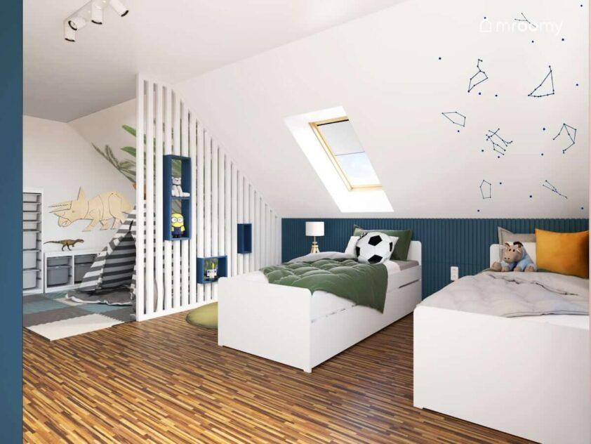 Strefa odpoczynku z dwoma białymi łóżkami oraz ścianą ozdobioną naklejkami z konstelacjami gwiazd w biało granatowym pokoju dwóch chłopców