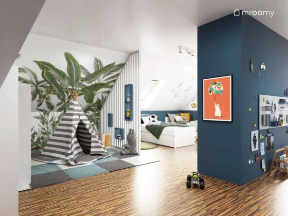 Biało granatowy pokój dla dwóch chłopców z dwoma łóżkami namiotem w paski na piankowych panelach podłogowych oraz tapetą w palmy