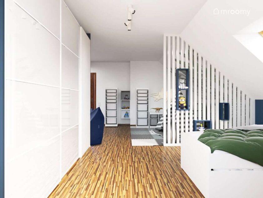 Duża biała szafa i wysokie regały z pojemnikami a także piankowe panele podłogowe i granatowe półeczki w przestronnym poddaszowym pokoju dwóch braci