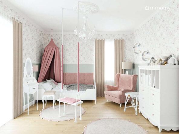 Łóżko ozdobione różowym baldachimem toaletka fotel oraz moduł z szufladami i przegródkami w jasnym pokoju małej dziewczynki zaś u sufitu ozdobny biały żyrandol i huśtawka