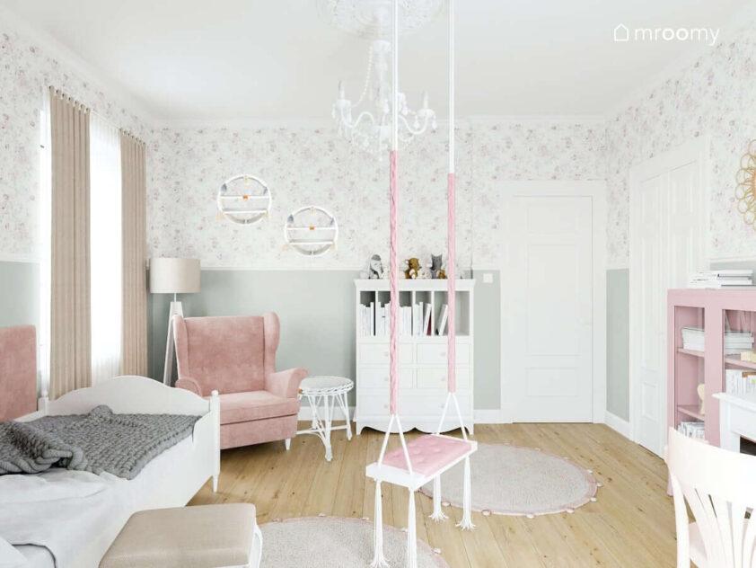 Przytulny pokoik dla małej dziewczynki utrzymany w jasnych odcieniach różu i bieli z fantazyjną huśtawką zawieszoną pośrodku pod ścianą meble modułowe z szufladami i przegródkami jasnoróżowy fotel i wiklinowe dodatki