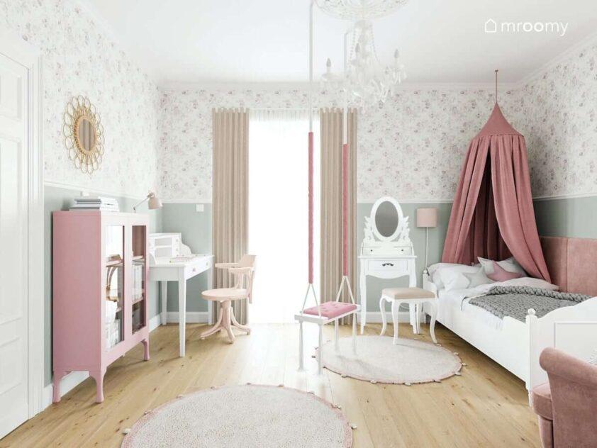 Biało różowy pokój małej dziewczynki z łóżkiem ozdobionym baldachimem toaletką i dużym żyrandolem na środku pokoju zawieszona huśtawka