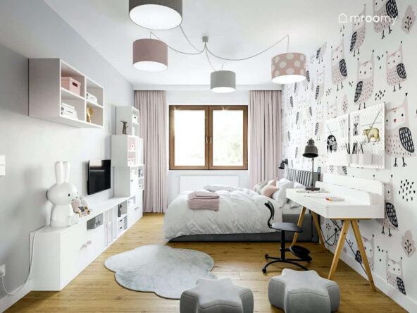 Jasny pokój dla dziewczynki w każdym w wieku w nim białe meble i różowo szare dodatki a na ścianie tapeta w sowy