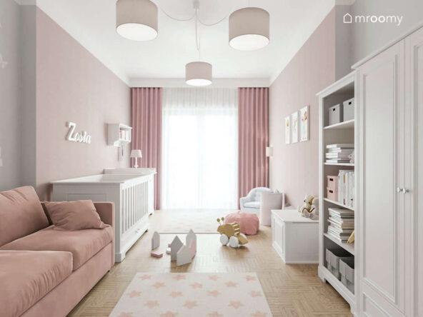 Biało różowy pokój z białą szafą regałem i łóżeczkiem oraz jasnoróżową sofą dla malutkiej dziewczynki a w nim okno ozdobione firanką i różowymi zasłonami a u sufitu duże lampy z różowymi abażurami