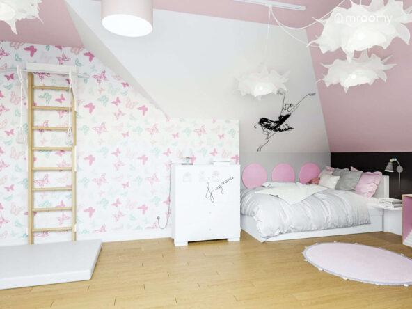 Drabinka gimnastyczna materac łóżko i komoda w biało różowym pokoju dziewczynki ozdobionym tapetą w motyle naklejką z baletnicą oraz miękkimi panelami ściennymi