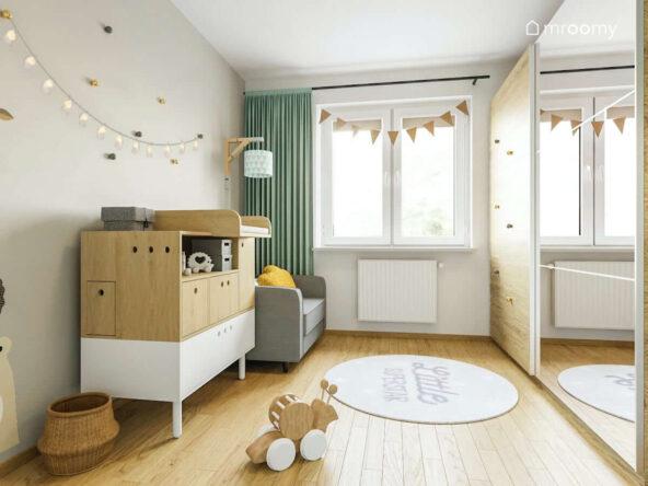 Pokój rocznej dziewczynki utrzymany w jasnych kolorach a w nim komoda z przewijakiem szary fotel duża szafa oraz ozdobne girlandy